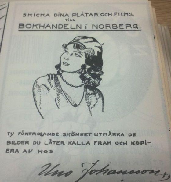 Tecknad annons: Porträtt av en kvinna i basker. Texten lyder: Skicka dina plåtar och films till bokhandeln i Norberg ty förtrollande skönhet utmärka de bilder du låter kalla fram och kopiera av oss.