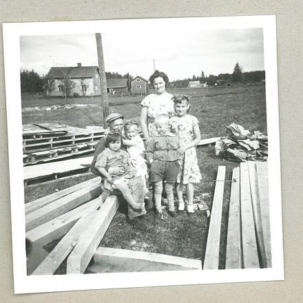 Ett svartvitt fotografi ur ett upphittat fotoalbum. Det ser ut som en familj med två vuxna, en kvinna och en man, och fyra barn. De sitter och står bland byggnadsmaterial.