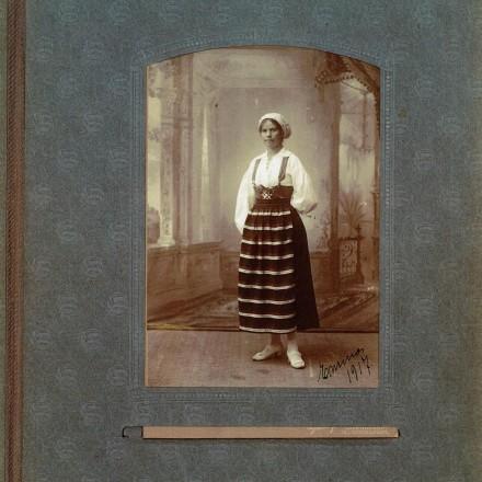 Bild av del ur gammalt fotoalbum. Ung flicka, Emma Åkerberg, i folkdräkt. Daterat 1917
