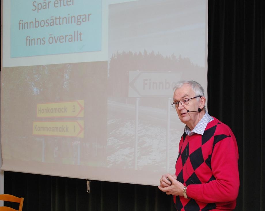 Seppo Remes med en bild ur sin powerpoint i bakgrunden