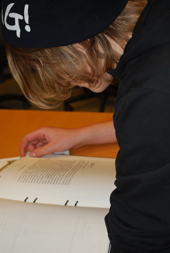 En ung pojke studerar arkivförteckningar. Hans hår hänger ned och döljer ansiktet.
