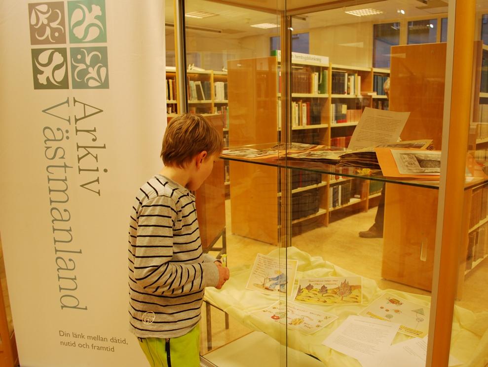 En pojke studerar Arkiv Västmanlands utställningsmonter på Engelbrektsgatan 3 i Västerås. I montern syns diverse foton och andra bilder.