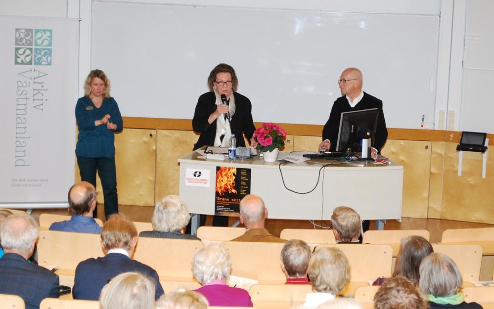 Ewonne Winblad föreläseer under seminariedagen Bränn skiten. På bilden syns från vänster Arkiv Västmanlands roll-up, en teckentolk, Ewonne Winblad och hennes man Lennart Winblad. I förgrunden nackarna på de främre radernas åhörare.