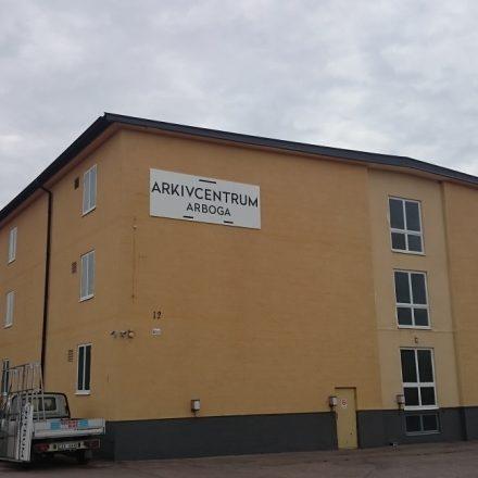 Gavel fasad Köpingsvägen 12. Skylt uppsatt med logotype för Arkivcentrum Arboga
