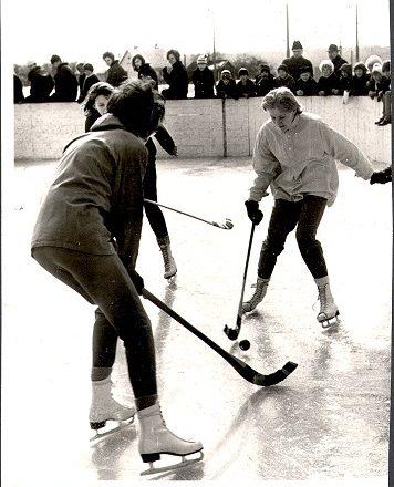 Tre damer spelar bandy i Kolsva på 1960-talet. I bakgrunden publik.